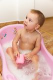 Cute little girl bathes in a shower Royalty Free Stock Images