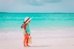 Cute little girl with beach bag and hat at sea. Coast Stock Image