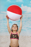 Cute little girl on beach with ball Stock Images