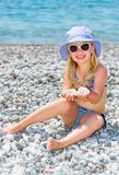 Cute little girl on the beach holds in the hands stones with ima Stock Photography