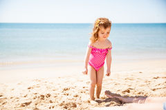 Cute little girl at the beach. Pretty little girl in a bathing suit having fun at the beach on a sunny day Royalty Free Stock Photography
