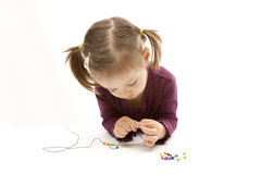 Cute little girl beading on white background Stock Images