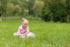 A cute little girl in a beautiful dress and sneakers playing in Stock Photos