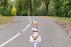 A cute little girl in a beautiful dress and sneakers playing on Royalty Free Stock Image