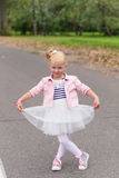 A cute little girl in a beautiful dress and sneakers playing on Royalty Free Stock Images