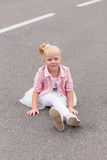 A cute little girl in a beautiful dress and sneakers playing on Stock Images