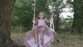Cute little girl in a beautiful pink dress riding on a swing. In nature, on a clear day stock video footage