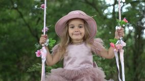 Cute little girl in a beautiful pink dress riding on a swing. In nature, on a clear day stock footage
