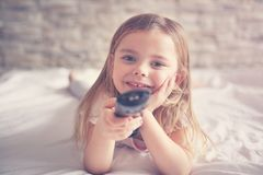 Cute little girl in bed. Little girl watching TV lying on bed with remote control in hand Stock Photos