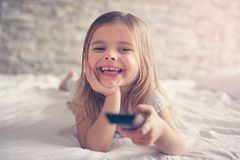 Cute little girl in bed. Little girl watching TV lying on bed with remote control in hand Stock Image
