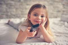 Cute little girl in bed. Little girl watching TV lying on bed with remote control in hand Royalty Free Stock Photo