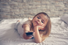 Cute little girl in bed. Little girl watching TV lying on bed with remote control in hand Royalty Free Stock Image