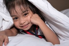Cute little girl on the bed woke up in the morning in her bed. soft white bed for a child, hiding under the blanket royalty free stock photography