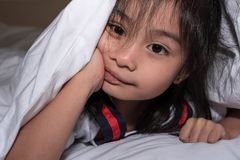 Cute little girl on the bed woke up in the morning in her bed. soft white bed for a child, hiding under the blanket stock image