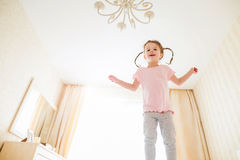 Cute little girl in bedroom jumping on a bed Royalty Free Stock Photography