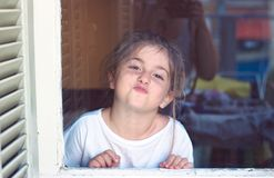 Free Cute Little Girl Behind The Window, Making Faces, Being Boring Stock Photo - 102628570