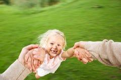 Cute little girl being spun in circles at park Stock Photos