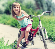 Cute little girl on bicycle in a park. Cute little girl on bicycle in green park Royalty Free Stock Photos