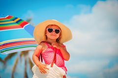 Cute little girl with big bag on beach. Cute little girl with big bag on tropical beach royalty free stock images