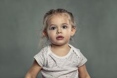 Cute little girl with big blue eyes. Gray background royalty free stock photo