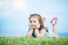 Cute little girl with big brown eyes. Lying on the grass Royalty Free Stock Photos