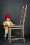 Cute little girl with big chair in studio Royalty Free Stock Images