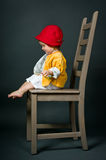 Cute little girl with big chair in studio Royalty Free Stock Photos