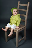 Cute little girl with big chair in studio Royalty Free Stock Photo
