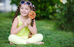 Cute little girl with big colorful lollipop. Stock Photos