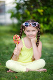 Cute little girl with big colorful lollipop. Royalty Free Stock Image