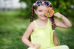 Cute little girl with big colorful lollipop. Little girl, brunette with long hair braided in two pigtails, in the ears of gold earrings, wearing sun glasses in Royalty Free Stock Image