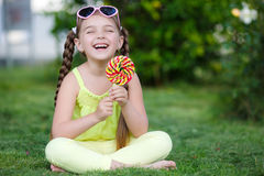 Cute little girl with big colorful lollipop. Royalty Free Stock Photos