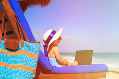 Cute little girl in big hat looking at laptop on Royalty Free Stock Image