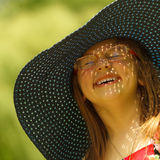 Cute little girl in big hat pretending to be lady Stock Photos