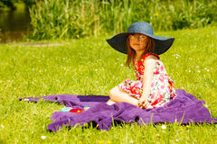 Cute little girl in big hat pretending to be lady. Cute little girl wearing big summer hat pretending to be woman lady. Child imitate mother playing in park Royalty Free Stock Photography