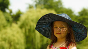 Cute little girl in big hat pretending to be lady. Cute little girl wearing big summer hat pretending to be woman lady. Child imitate mother playing in park Royalty Free Stock Photos