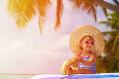 Cute little girl in big hat on summer beach Stock Image
