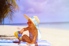 Cute little girl in big hat on tropical beach Stock Photos
