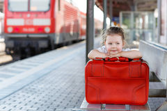 Cute little girl with big red suitcase on a railway station Royalty Free Stock Images