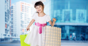 Cute little girl in big wear with packages Royalty Free Stock Images