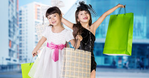 Cute little girl in big wear with packages Royalty Free Stock Image