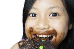 Cute little girl biting chocolate bar on studio. Image of cute little girl biting chocolate bar with happy expression,  on white background Stock Photo