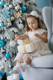 Cute little girl in bklom dress sitting in a chair and opens  box with  present for background Christmas tree  blue Royalty Free Stock Image