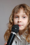 Cute little girl with black microphone. Stock Photos