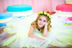 Cute little girl with blond curls in a white lush dress with giant sweets in pink background stock images