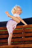 Cute little girl with blond curly hair. Playing on wooden chain swing Royalty Free Stock Photo