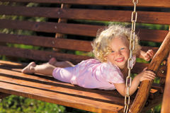 Cute little girl with blond curly hair. Playing on wooden chain swing Stock Photo