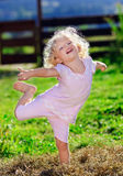 Cute little girl with blond curly hair playing. On green lawnwith hay heap Stock Image