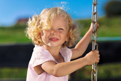 Cute little girl with blond curly hairs. Cute little girl with blond curly hair playing on wooden chain swing Stock Photography