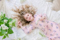Cute little girl with blond hair in a beautiful dress in a spring studio with lilac. Flowers royalty free stock photography